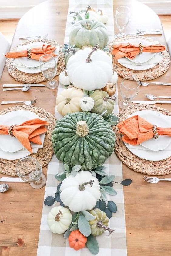 a simple and cozy bright Thanksgiving tablescape with a plaid runner, orange napkins, heirloom pumpkins, greenery and woven placemats