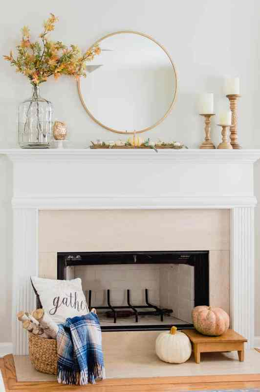 a simple and lovely rustic mantel with faux pumpkins and greenery, bold dried leaves, pillar candles in wooden candleholders