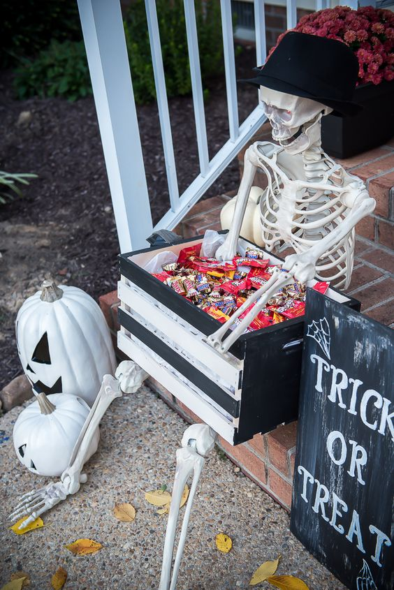 a skeleton in a hat holding a crate with sweets and chocolate is a great idea for kids that will come for treat or trick