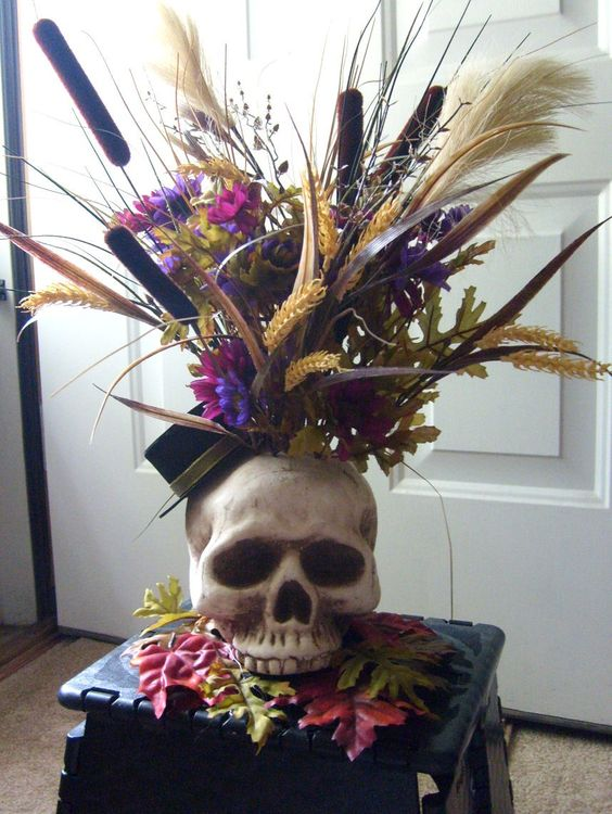 a skull vase with bold blooms, grasses and bright faux flowers is a lovely idea for Halloween, it can be used as a centerpiece