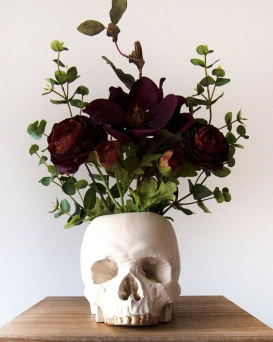 a skull vase with dark blooms and greenery is a lovely decoration or Halloween centerpiece you can easily DIY