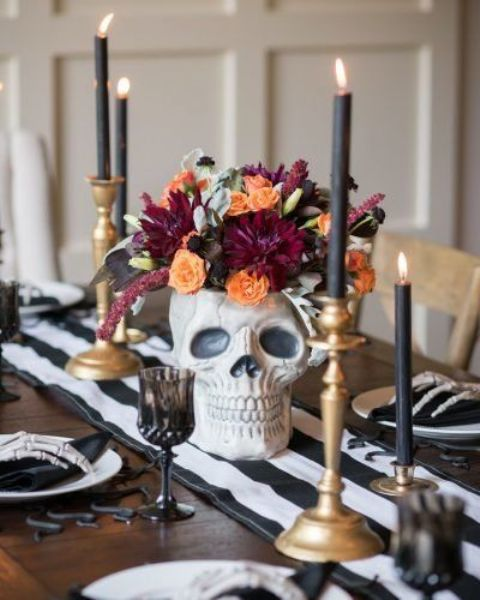 a skull vase with orange, burgundy and black blooms and pale leaves plus candles around is a stylish solution to rock