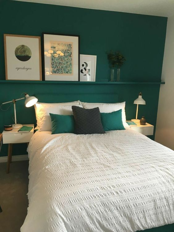 a small and bright bedroom with an emerald accent wall, a matching bed and pillows, small white nightstands with table lamps and a ledge with art