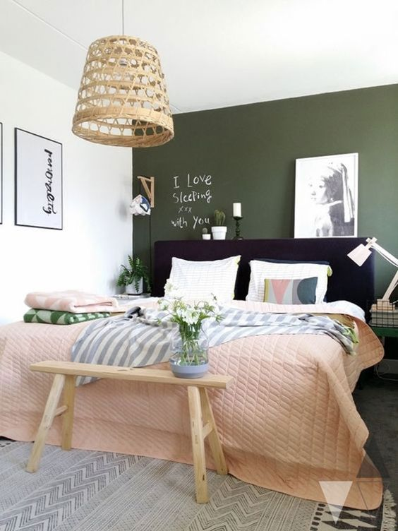 a small and cute bedroom with a dark green accent wall, a navy upholstered bed, neutral and pastel bedding, a woven pendant lamp and some artworks