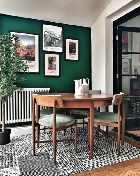 a small and lovely dining nook with an emerald accent wall, a mini gallery wall, a round table and green chairs, a bold printed rug