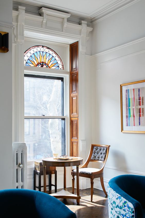 a small and lovely nook with a tall window with stained glass in the upper part, a coffee table and a chair and a bold artwork that echoes with the window