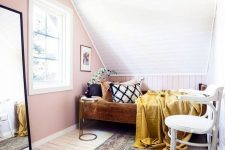 a small attic bedroom with a pink accent wall, a bed with colorful bedding, a white chair, a mirror in a black frame and a boho printed rug