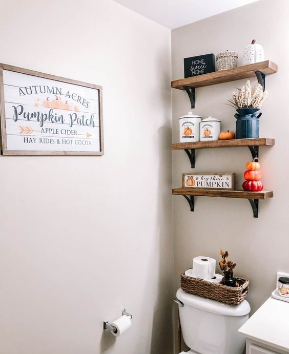 a small bathroom styled with colorful faux pumpkins, jars with pumpkins, a cool planked signage and some wheat in a black vase