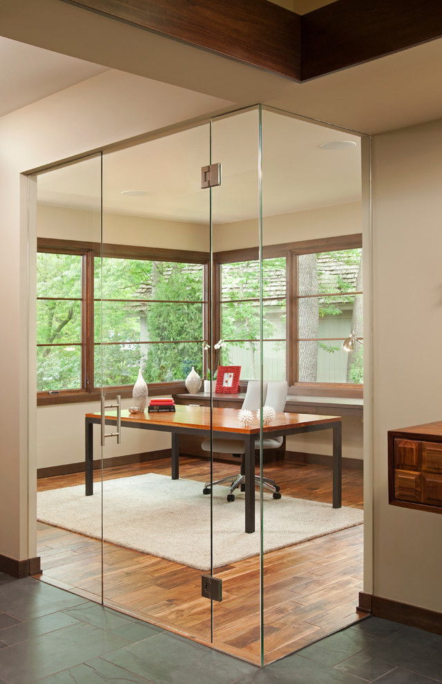 a small home office nook with window walls and glass doors that separate it to keep the person focused inside it