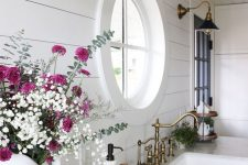 a small white farmhouse kitchen with a porthole window, vintage sconces and appliances, a white stone countertop