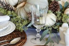 a soft and natural Thanksgiving tablescape with woden placemats, white plates and neutral pumpkins, greenery and pinecones is amazing
