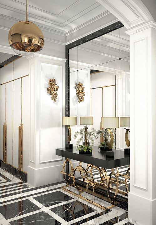 a sophisticated black and white entryway with a geometric floor, a mirror wall, a black console table with brass legs, brass handles on wardrobes and a brass globe pendant lamp