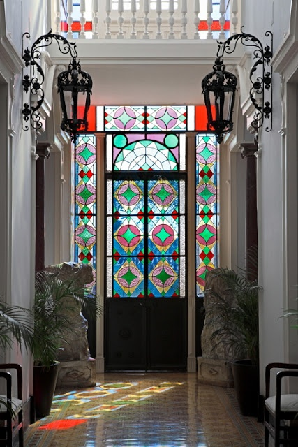 a sophisticated entry with a stained glass metal door and sidelights and vintage black outdoor lamps is gorgeous