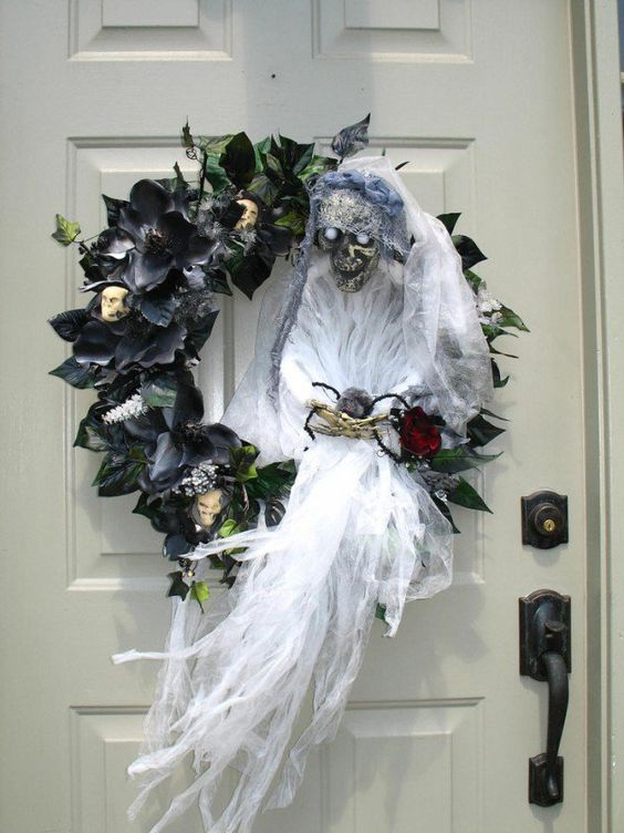 a spooky Halloween wreath of black faux blooms and leaves, skulls, a ghost with a bloom is jaw-dropping