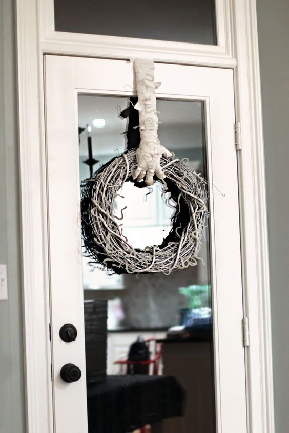 a spooky and cool Halloween wreath of vine holded by a mummy hand is a very fresh and catchy piece to make yourself