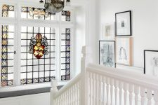 a staircase with a large window with stained glass and a built-in windowsill seating plus a gallery wall and a chic chandelier