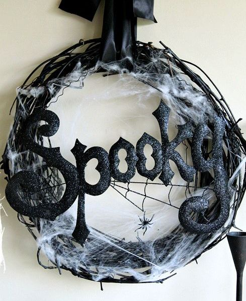 a stylish and scary black Halloween wreath of vine, spiderweb, spiders, glitter letters and a silk ribbon bow is pure chic