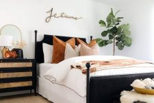 a stylish bedroom with a black bed, a black dresser, a black chest that doubles as a bench, pumpkins in a bowl and wheat in a vase