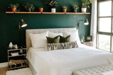 a stylish boho bedroom with a dark green accent wall, a long shelf with potted plants, a neutral upholstered bed and a bench, a brown Moroccan pouf and glass nightstands