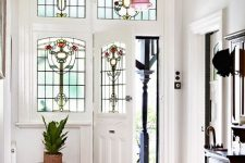 a stylish entryway with sidelights and a door with stained glass, a dark storage unit and a rack, a bold rug and a matching pendant lamp