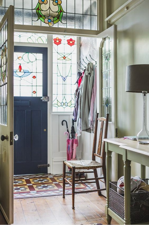 a stylish entryway with sidelights and the door with stained glass, a vintage green console table and a chair, a bold printed rug