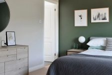 a stylish modern bedroom with a dark green accent wall, a grey bed with bold bedding, a printed rug and a stained sideboard plus a mini gallery wall