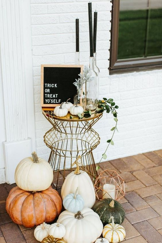 a stylish modern display with lots of pumpkins, geometric lanterns, black candles and a black framed sign