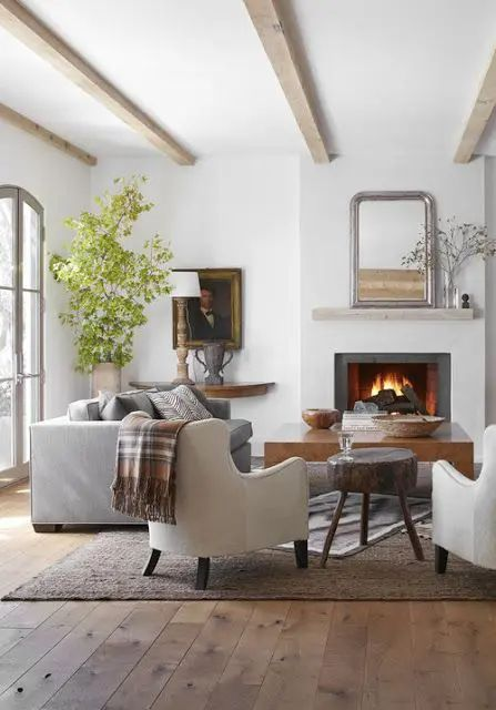 a stylish neutral living room with light-stained woodne beams, a fireplace, a slab table, neutral seating furniture and a potted tree