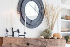 a stylish rustic fall mantel with a black candelabra with tall candles, natural heirloom pumpkins and wheat in a vase plus a mirror in a cool black frame