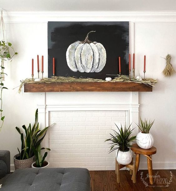 a stylish rustic fall mantel with grass, bold orange candles, a chalkboard pumpkin is a laconic and delicate decor idea