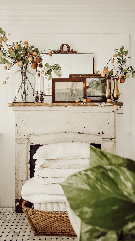 a subtle and cool fall mantel with gold and clear vases with branches with pears, some artworks in lovely frames, metal candleholders with white candles