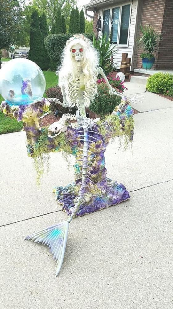 a super eye-catchy mermaid skeleton with seashells and moss is a cool idea for Halloween decor but in an unusual way