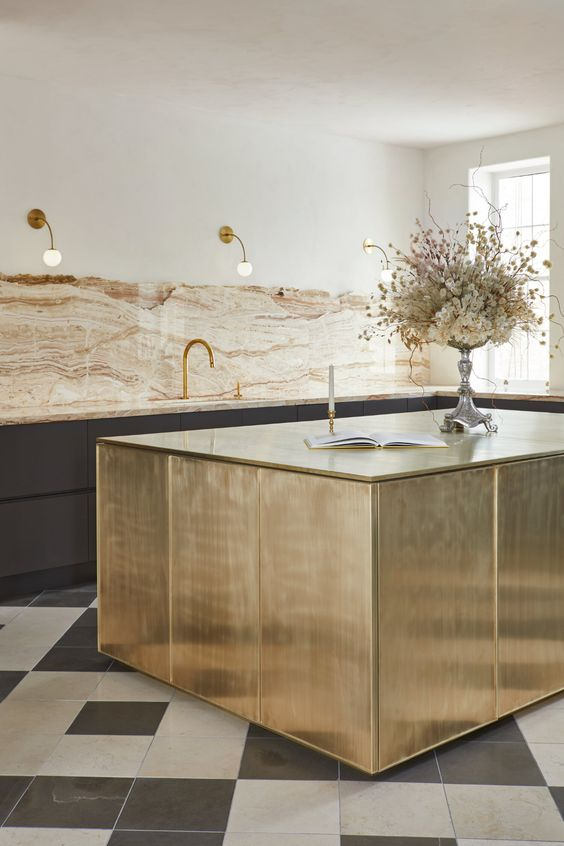 a unique sophisticated kitchen with black lower cabinets, an earthy tone stone backsplash and countertops, a brushed brass kitchen island and sconces