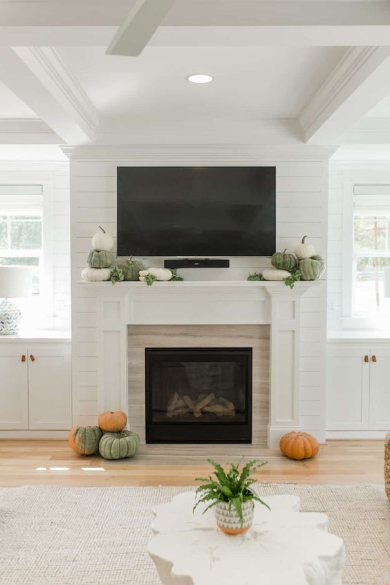a very simple and laconic fall mantel with heirloom pumpkins stacked and some greenery plus some pumpkins around the fireplace