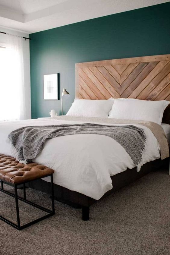 a very simple farmhouse bedroom with a bed with a chevron wooden headboard, a leather bench, neutral nightstands and neutral bedding