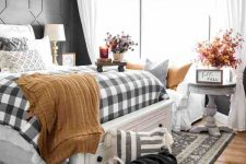 a vintage famrhouse bedroom with black paneled walls, a white bed with drawers, plaid and mustard bedding, a basket with a pillow and some fall leaf arrangements