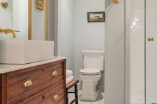 a vintage grey bathroom with a rich-stained vanity, a square sink, brass fixtuers and lamps on brass legs is gorgeous