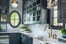 a vintage navy kitchen with shaker cabinets, a white subway tile backsplash and stone countertops, brass pendant lamps, fixtures, handles
