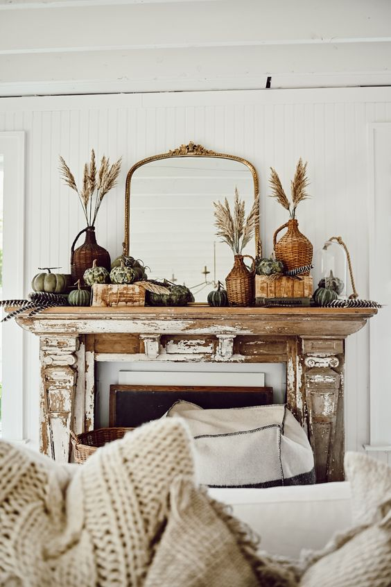 a vintage rustic fall mantel with wheat in woven bottles, heirloom and faux pumpkins, books and a mirror in an ornated frame is chic