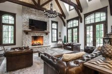 a vintage rustic living room with dark-stained wooden beams, brown leather sofas, a large fireplace clad with stone, a large chandelier of metal