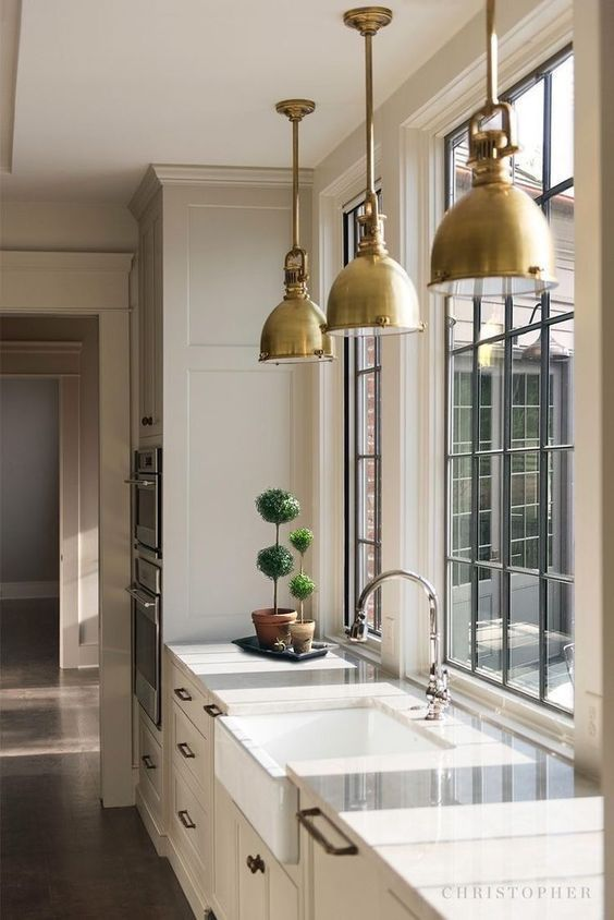 a vintage tan kitchen with white stone countertops, windows instead of a backsplash, brass vintage pendant lamps and topiaries is wow