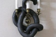 a wall candelabra covered with a faux black snake is a cool solution for Halloween and is very easy to DIY