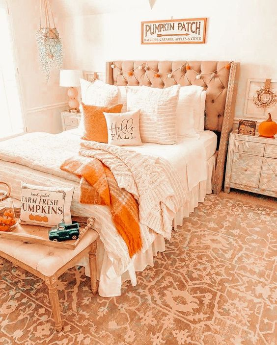 a warm-colored fall bedroom with a tan upholstered bed and neutral bedding, an upholstered bench, mirrored nightstands, neutral and orange bedding and a pompom garland plus a pumpkin pillow