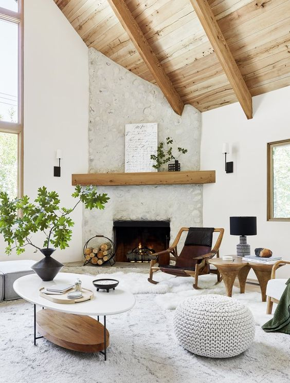 a welcoming bright living room with a fireplace clad with stone, wooden beams, catchy furniture, a large rug and a knit pouf plus greenery