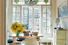 a welcoming home office with a large window with stained glass, cool modern furniture and a chic chandelier plus tiles on the floor