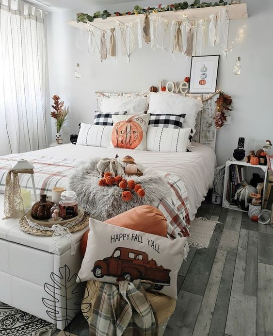 a whimsy fall bedroom with a shabby chic bed, a white bench with storage, pillows and lights, a tassel garland, plaid pillows and blankets, pumpkins and candles