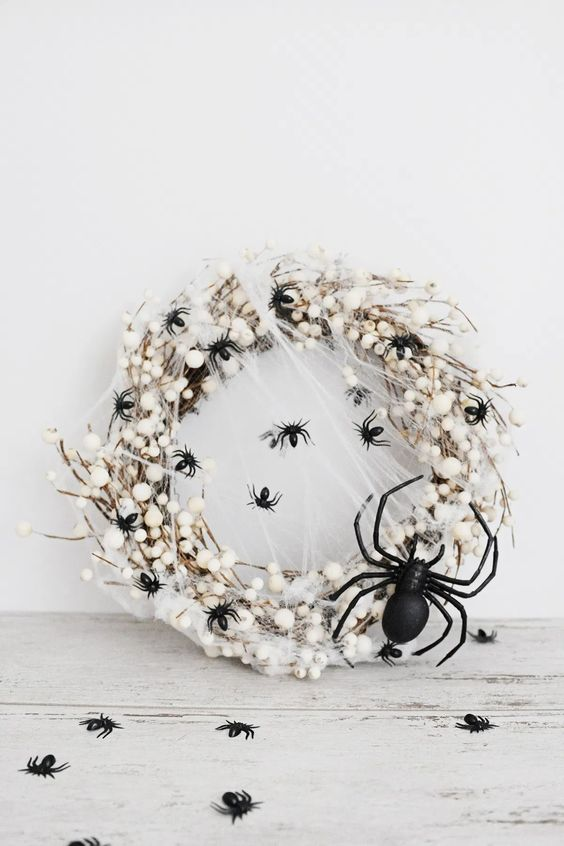 a white Halloween wreath of vine, black spiders, spiderwebs, some white pompoms and a giant spider for a statement is wow