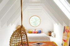 a white attic bedroom with bright textiles, a round window, bold pillows and a cool rattan pendant chair is amazing