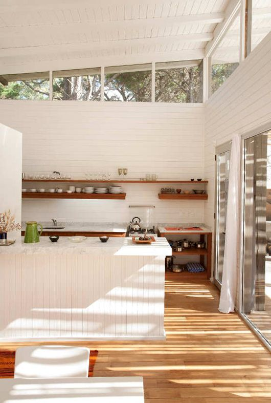 a white cabin kitchen with beadboard cladding the walls and clerestory windows that bring light inside and sliding doors