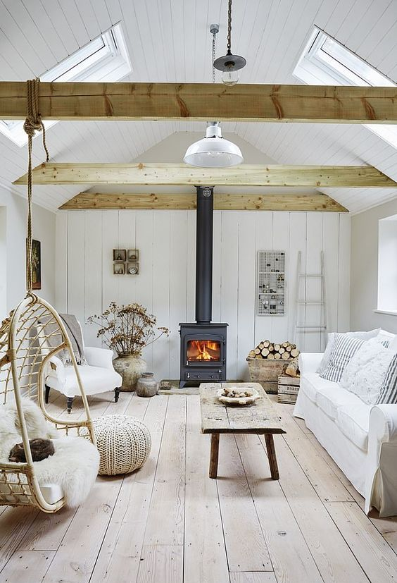 a white coastal liivng room with planked walls and a floor, light-stained beams, a hearth, white seating furniture and a weathered wood table